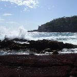 Waves crashing into red sands bay (103015)