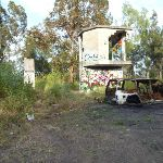 Derelict buildings and a burnt out car at the end of Belmont Lagoon (390389)